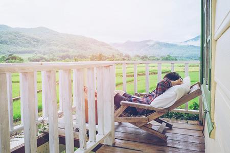 Junger Mann relaxt auf der Terrasse