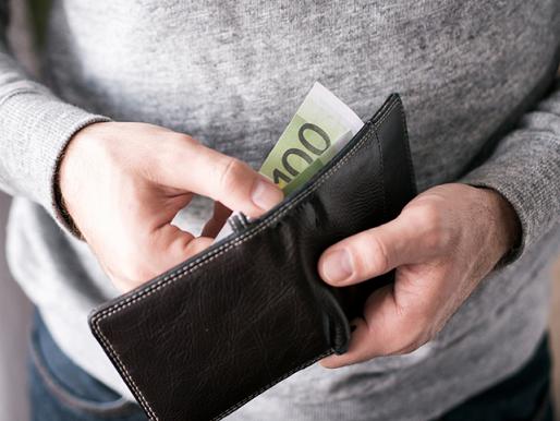 Mann nimmt Euroschein aus der Geldbörse
