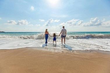 Familie mit Kind steht am Strand in der Brandung.