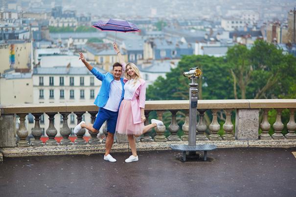 Junges Paar steht mit Regenschirm glücklich vor Geländer.