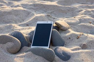 Smartphone auf Steinen im Sand an der Nordsee